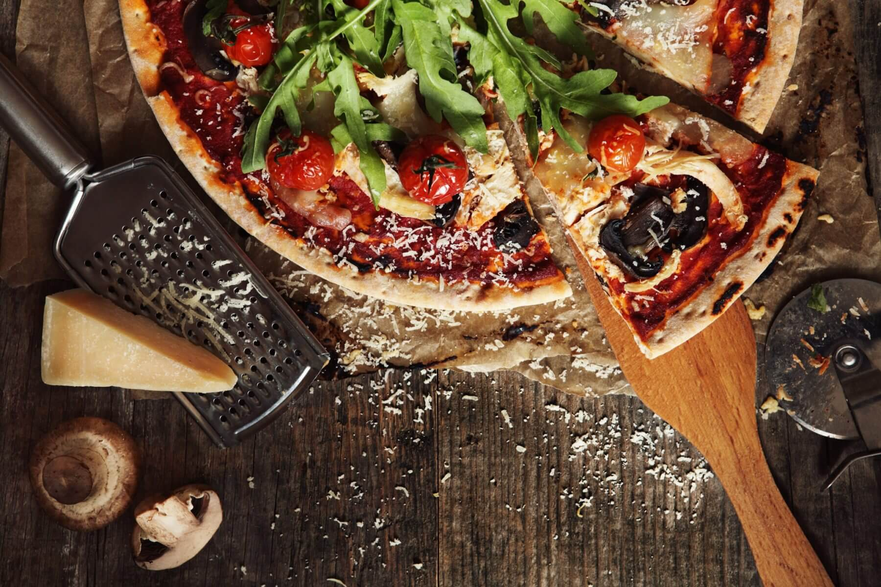 Overhead view of a pizza and ingredients on table