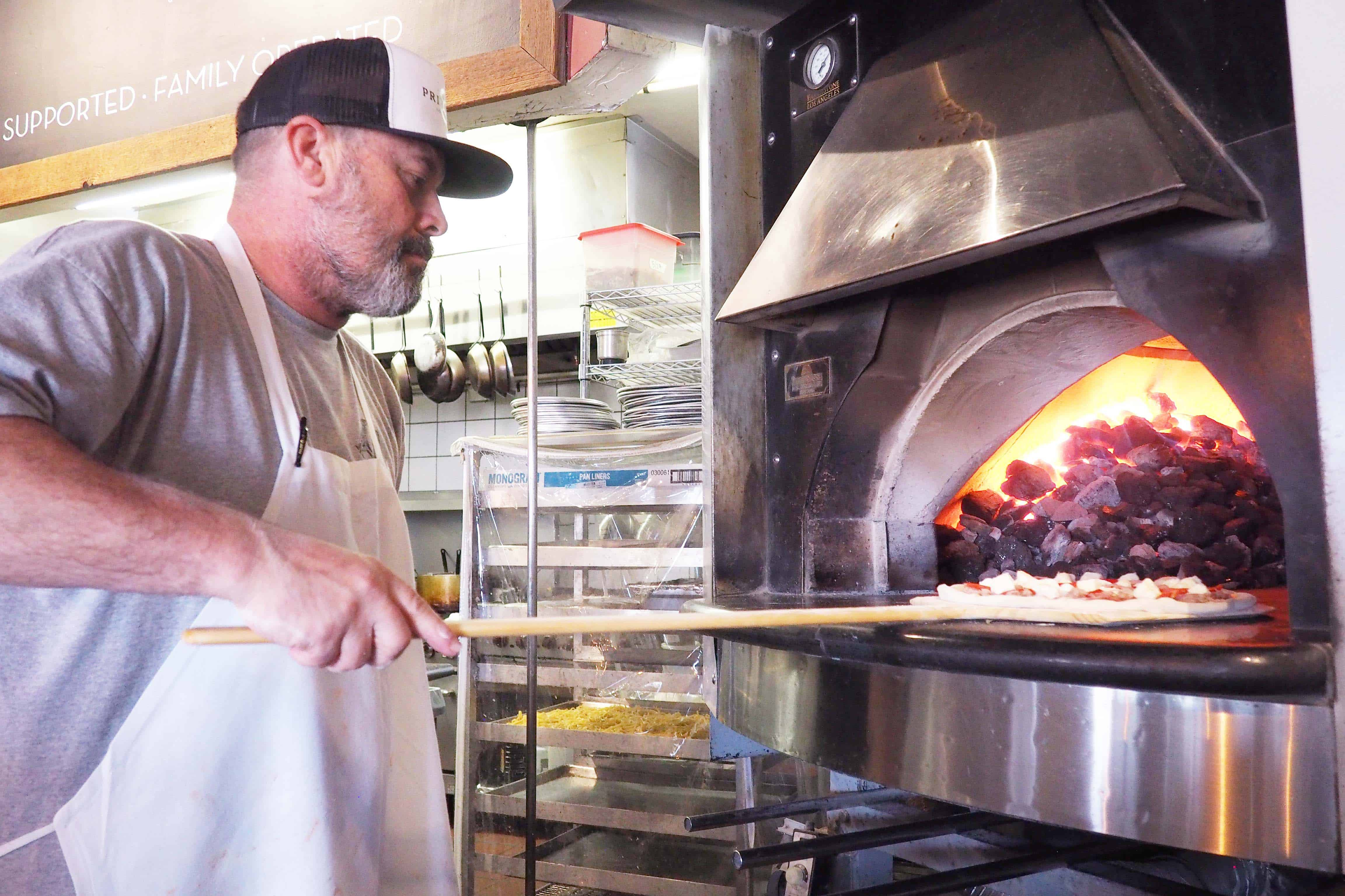 Chef Shannon Sager Cooking Pizza in a Coal Fire Oven